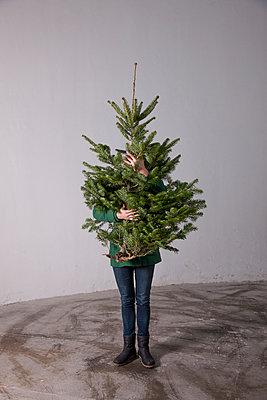 Woman hiding behind Christmas tree - p1231m1138514 by Iris Loonen