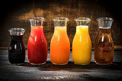 Row of five glass bottles of various fruit juices - p300m2023530 von Roman Märzinger