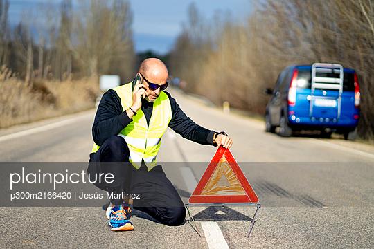 Man using a smartphone having a car breakdown - p300m2166420 by Jesús Martinez
