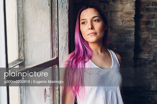 Portrait of a stylish young woman with pink hair in loft - p300m2202818 by Eugenio Marongiu