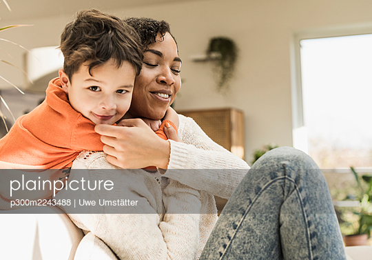 Smiling boy embracing mother while playing at home - p300m2243488 by Uwe Umstätter