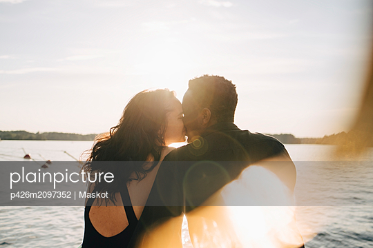 Multi-ethnic couple kissing while sitting against lake during summer - p426m2097352 by Maskot
