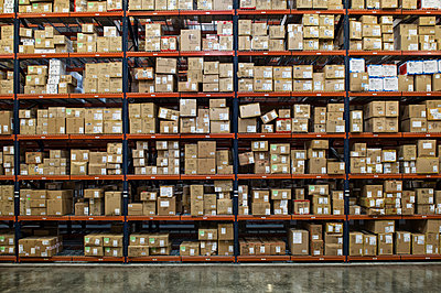 View of racks of cardboard boxes containing product in a large distribution warehouse. - p1100m1575486 by Mint Images