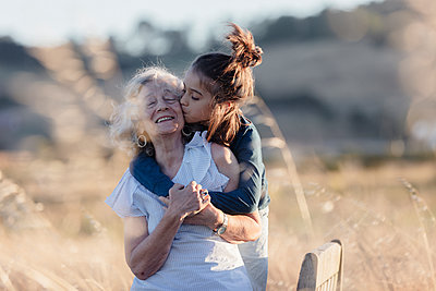 Grandson kissing grandmother while standing on field - p1166m1489572 by Cavan Images