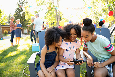 Sisters using smart phone at summer neighborhood block party in park - p1192m2016990 by Hero Images