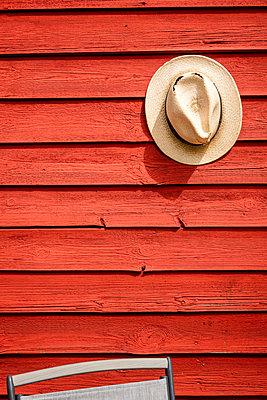 Straw hat hanging on wall - p1418m2195610 by Jan Håkan Dahlström