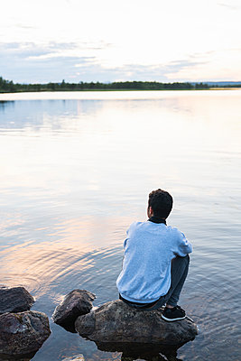 Finland, Lapland, man sitting on a rock in a lake - p300m2060839 by Kike Arnaiz