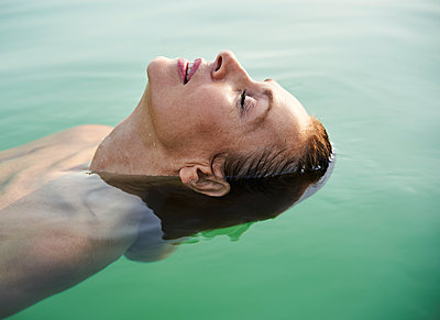 Mature woman floating in a lake with closed eyes - p300m2140680 by Philipp Nemenz