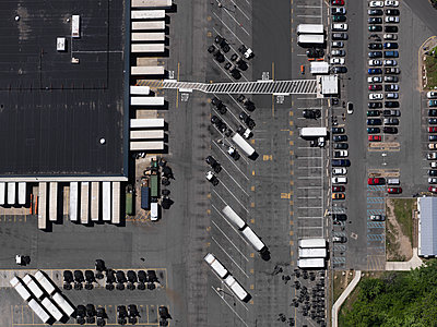 Aerial view sunny parking lot and commercial warehouse, New York City, New York, USA - p301m2017496 by Stephan Zirwes