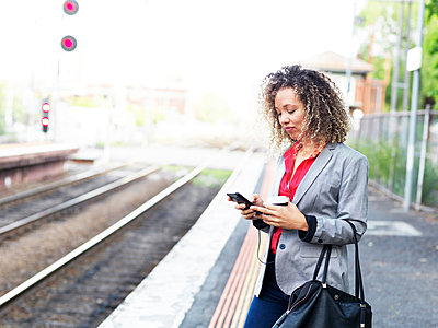 Mid adult woman standing on train platform, using smartphone, holding disposable coffee cup - p924m1559861 by Elke Meitzel
