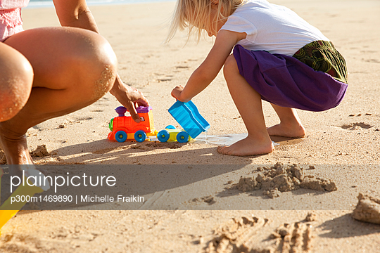 Spain, Fuerteventura, mother and daughter playing on the beach - p300m1469890 by Michelle Fraikin