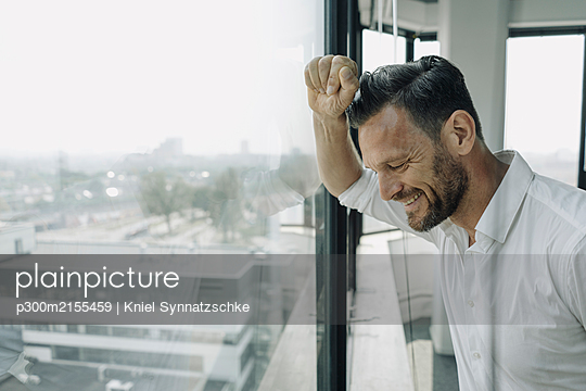 Mature businessman looking out of window in office - p300m2155459 by Kniel Synnatzschke