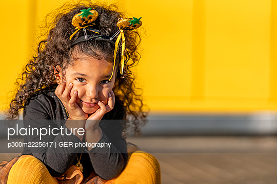 Girl sitting with head in hands against yellow wall - p300m2225617 by GER photography