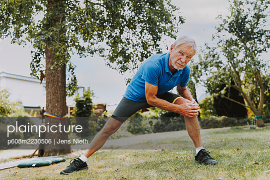Elderly man doing stretching exercise in the garden - p608m2230506 by Jens Nieth