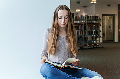 Teenage girl reading book in a public library - p300m1450241 by Tom Chance