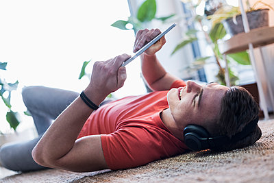 Man watching video on digital tablet while lying on carpet in living room - p300m2267467 by Uwe Umstätter