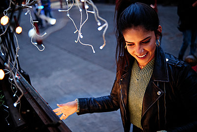Smiling young woman spending leisure time in city - p300m2273692 by Angel Santana Garcia