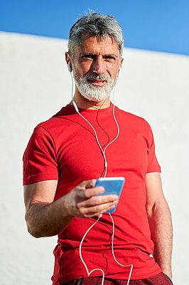 Mature man with headphones using smart phone by wall - p300m2275691 by Kiko Jimenez