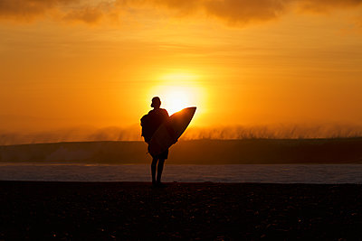 Silhouetted male surfer watching ocean wave from sunset beach - p301m2148965 by Nik West