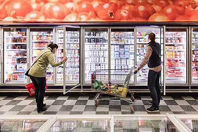 Couple choosing at refrigerated section in supermarket - p426m1148144 by Maskot