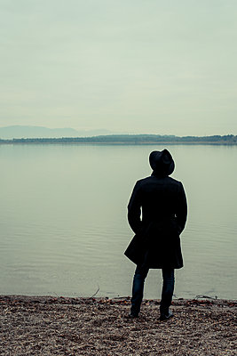Man with hat stands on the waterfront - p750m1497088 by Silveri