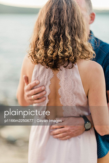 couple sharing a hug by the water during sunset together - p1166m2250677 by Cavan Images
