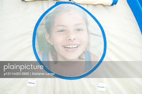 Mädchen blickt lachend durch Zeltfenster - p1311m2013905 von Stefanie Lange