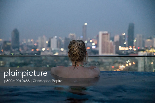 Thailand, Bangkok, back view of woman bathing in Infinity Pool looking at skyline - p300m2012466 von Christophe Papke