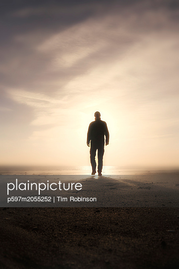 Silhouette man walking towards camera with sun behind - p597m2055252 by Tim Robinson