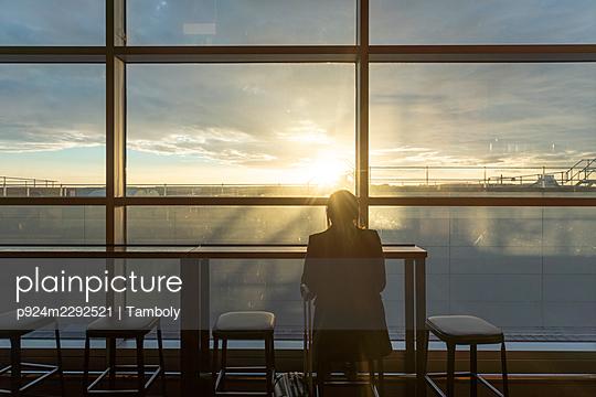 UK, London, Rear view of woman at airport terminal at sunset - p924m2292521 by Tamboly