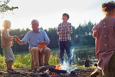 Grandfather and grandchildren enjoying campfire at lakeside - p1023m1172713 by Francis Pictures