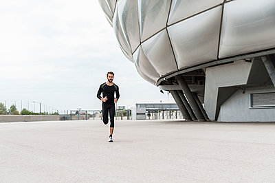 Man running at stadium - p300m1586967 by Daniel Ingold