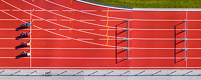 Germany, Baden-Wurttemberg, Winterbach, Aerial view of female hurdlers kneeling on starting line - p300m2155812 by Stefan Schurr