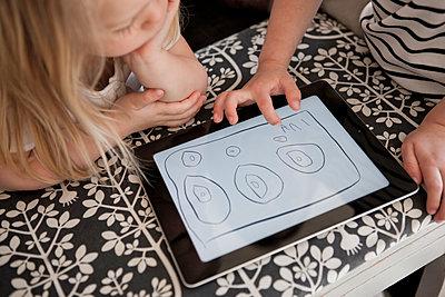Children using digital tablet - p312m1075900f by Peter Rutherhagen