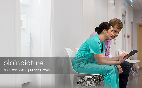 Nurse with clipboard talking to patient - p300m1166100 by Milton Brown