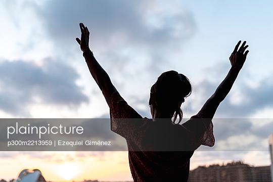 Woman standing arms raised watching sunset - p300m2213959 by Ezequiel Giménez