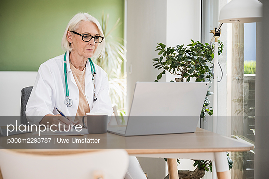 Female doctor writing while working at desk - p300m2293787 by Uwe Umstätter