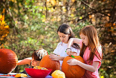 Three Young Children Carving Pumpkins Outdoors - p1166m2147172 by Cavan Images