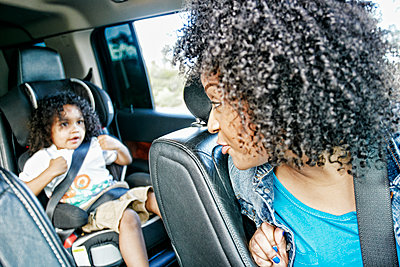 Mixed race and mother checking daughter in car seat - p555m1523008 by Peathegee Inc