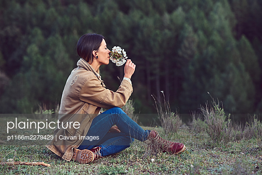 Woman on the mountain. She is in a forest with pine trees. - p1166m2279429 by Cavan Images