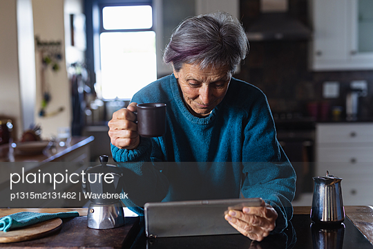 Senior woman drinking coffee and using tablet at home - p1315m2131462 by Wavebreak