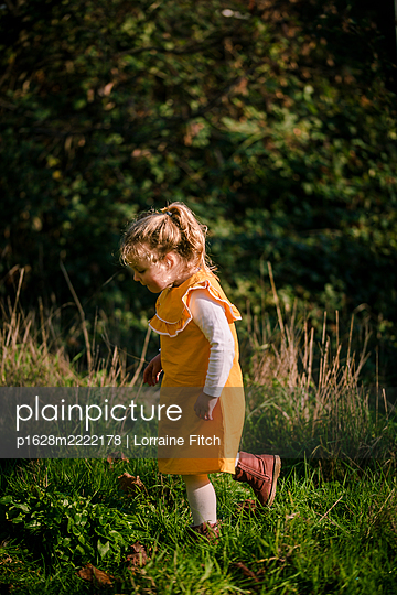 Toddler in yellow dress running over grass - p1628m2222178 by Lorraine Fitch
