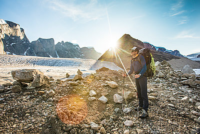 Backpacker standing on glacial moraine in Auyuittuq National Park - p1166m2205805 by Cavan Images