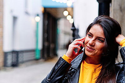 Smiling woman talking on mobile phone in city - p300m2273668 by Angel Santana Garcia