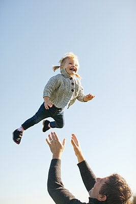 Female toddler thrown mid air by father against blue sky - p924m1422873 by Sasha Gulish