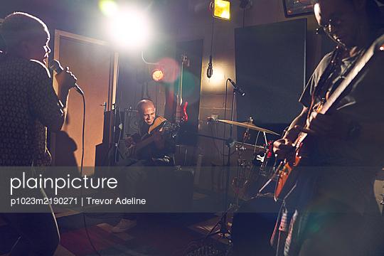 Musicians practicing in recording studio - p1023m2190271 by Trevor Adeline