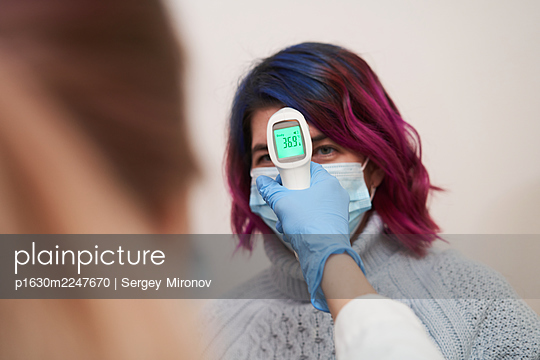 Doctor measuring patient's temperature by contactless thermometer - p1630m2247670 by Sergey Mironov