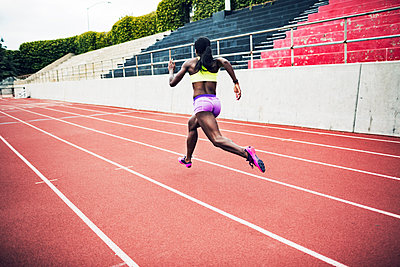 Rear view of determined athlete running on tracks - p1166m1086171f by John Trice