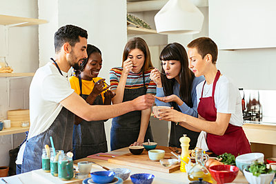 Friends tasting food in a cooking workshop - p300m1588035 von Bonninstudio