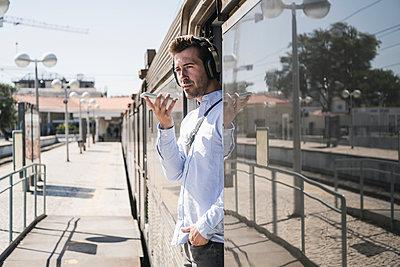 Young man with headphones using smartphone in train door - p300m2156720 by Uwe Umstätter